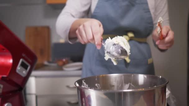 Kuchař vloží smetanový tvaroh do misky planetárního mixéru.