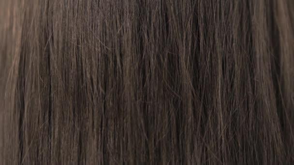 Demonstration of the brunettes hair before straightening it