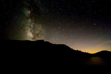Milky Way above black silhouette of mountain with sunset glow re