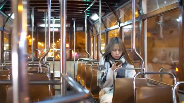 Hong Kong - January 22, 2020: A beautiful Chinese woman alone at night on a train holding a phone in winter.