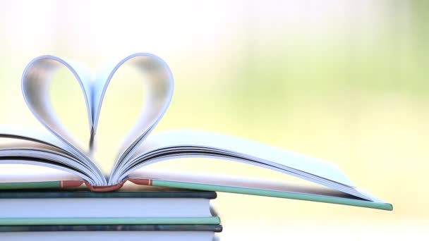 Book stack open page heart shape in wind.