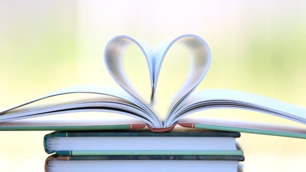 Bücherstapel offene Seite Herzform im Wind.