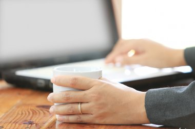 Business woman hold a coffee cup and using laptop computer