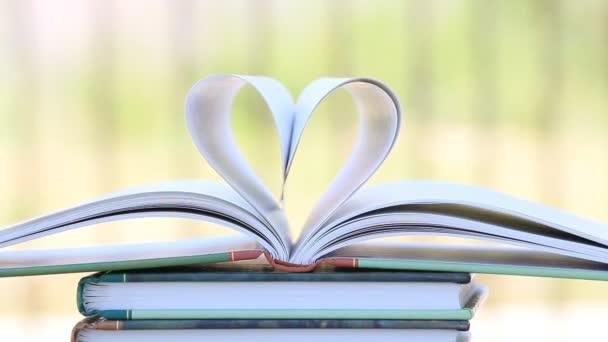 Bücherstapel offene Seite Herzform im Wind, grüner Garten Hintergrund