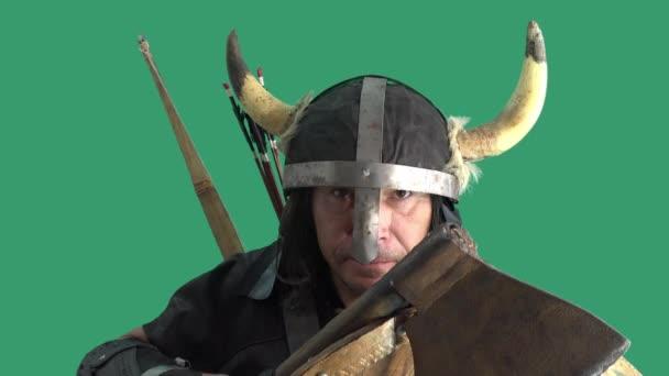 Zpomal. Do dřevěného štítu Vikingského válečníka udeřil šíp. Starší muž v helmě s rohy a sekerou v rukou. Zelené pozadí