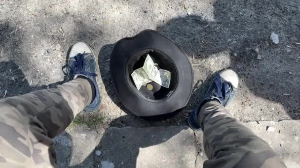 Top view of a hat with money, homeless, unemployed asks for alms, help. Man throws money into his hat