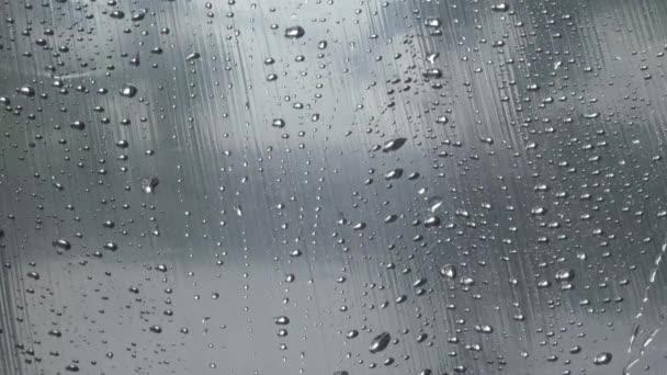 Goccioline di acqua da pioggia su vetro flusso giù macro