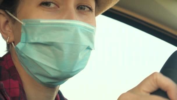 Junge Autofahrerin mit medizinischer Maske, um die Ausbreitung von COVID-19 zu verhindern. Autofahrerin mit Gesichtsmaske im Auto zum Schutz vor Virusgrippe