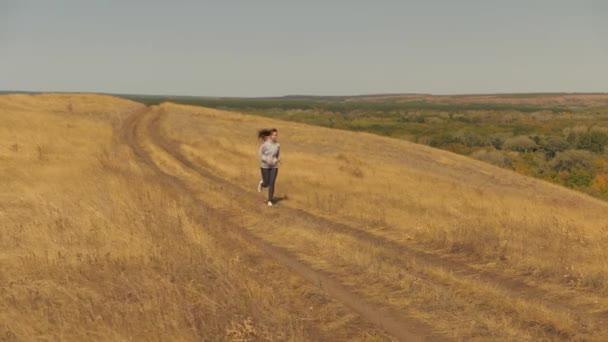 Gesunde schöne Mädchen beschäftigt sich mit Fitness, Joggen auf dem Land. Trainingsjogging. Junge Frau läuft im Sommer im Park Joggerin atmet frische Luft