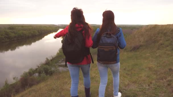 Female travelers with backpacks are walking along a high mountain and smiling. Girlfriends hiking trip. Life adventures of women in nature. Teamwork. Family weekend together by the flowing river