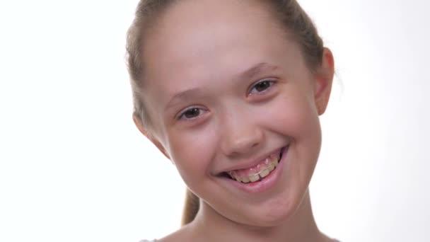 Boldog kislány mosolyog fogakkal fehér, elszigetelt háttérrel. Harapásjavító tányér és görbe fogak. A gyermek mosolykorrekciót végez a fogorvosnál. Indikációk a