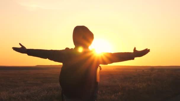 Der freie und glückliche männliche Tourist hob die Hände und genoss die inspirierende Luft bei Sonnenuntergang am Himmel. Ein Mensch ist allein in der Natur unterwegs. Ein Tourist, der den Sieg errungen und das Ziel erreicht hat