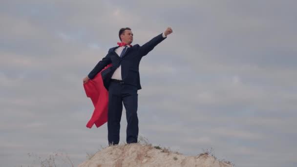 Egy vörös köpenyes szuperhős a kék ég ellen, egy szmokingos üzletember, gyors siker az üzletben, a vállalat fő statisztikáinak vezetője, egy menedzser, aki új felfedezéseket tesz