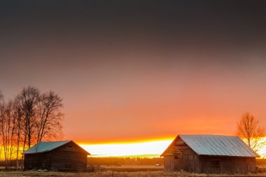 Last Rays Of Sun Behind The Barn Houses