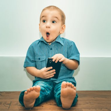 Surprised little boy with a cell phone
