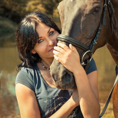 Portrait of a beautiful young woman with a horse.