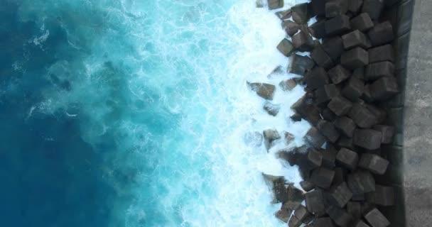 Anténa (pohled shora). Letu nad oceánem pobřeží Tenerife. Tmavě tyrkysové vody, bílý a tmavý kamenné kostky molo. Abstraktní pozadí videa pro tituly. 4k