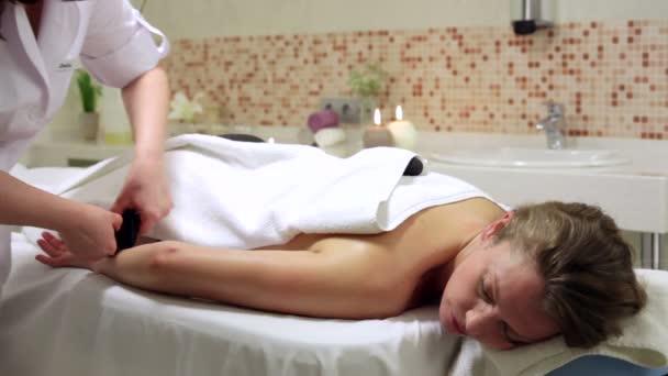 Žena se těší kamenné terapie. Žena přijímá, relaxační masáž