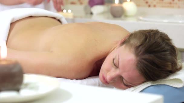 Frau genießt Steintherapie. Frau erhält eine entspannende Massage-Behandlung