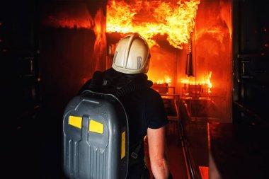 Gönüllü itfaiyeci yangını söndürmek ve insanları kurtarmak için yangın odasına giriyor. İtfaiyeci dumanlı odalara girmek için oksijen tüpleri kullanır. Yanan binaya arkadan giren itfaiyeci.