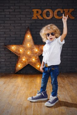 Little Boy Rock Star Giving The Rock And Roll Sign