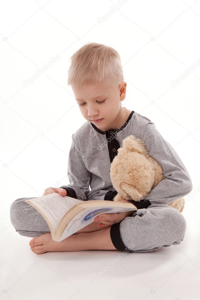 e1367822d8 Niño en pijama con su oso de peluche y un libro aislado sobre fondo blanco  aislado