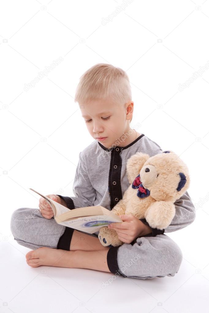 3cd1987ba6 Niño en pijama con su oso de peluche y un libro aislado sobre fondo blanco —