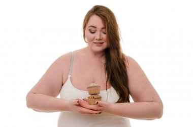 A fat woman with a muffin in her hand isolated on white background