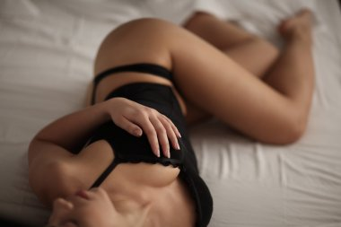 Beautiful young woman showing off her butt while lying bed