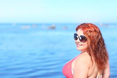 Redhead woman in sunglasses resting on beach