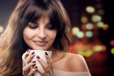 Beautiful brunette woman holding a cup of hot beverage, coffee or tea. Portrait. stock vector
