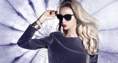 Beautiful fashionable young blonde woman posing in studio wearing sunglasses. stock vector