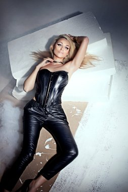 Sexy beautiful blonde woman posing in leather costume, looking at camera. Sensual photo. stock vector