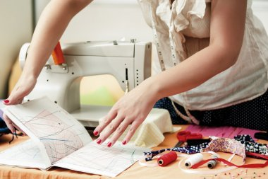 Young Woman is Sewing at Home