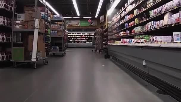 Snellville, Ga USA - 08 15 20: Walmart Neighborhood Market grocery store covid-19 pandemic worker wearing a face mask stock on the floor and on carts
