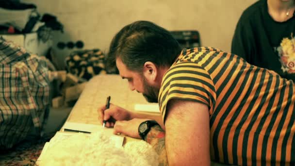 Man drawing with pencils and pens on floor