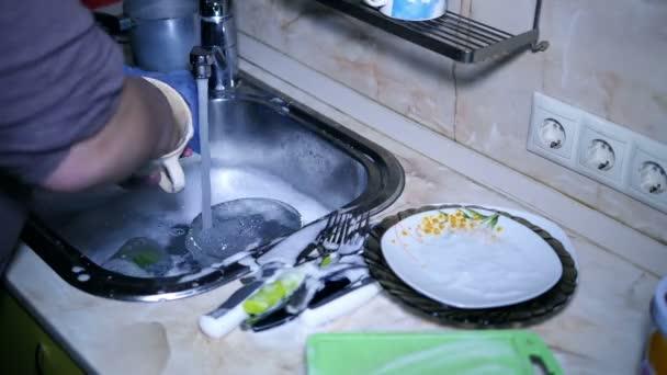 der Mann in der Küche spült Geschirr in der Spülbürste im Zeitraffer