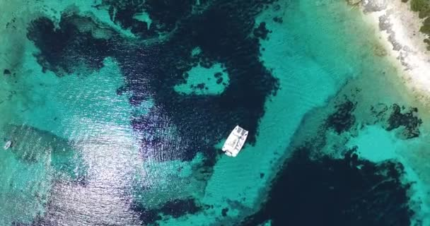 Aerial, top drone scene of catamaran anchored in a bay with transparent turquoise water and patterned bottom.