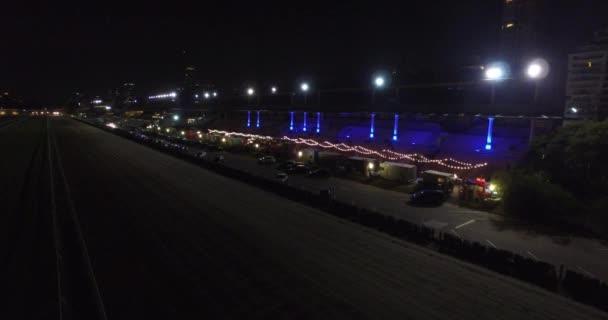 Letecká scéna ze stadionu v noci s pěší ulice s bary ve středu