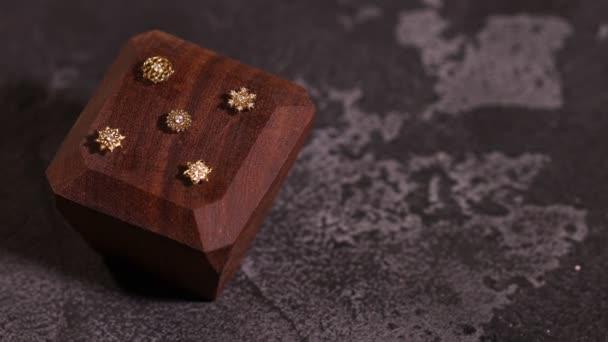 Beautiful piercing jewelry on wooden display rotate. Macro shot.