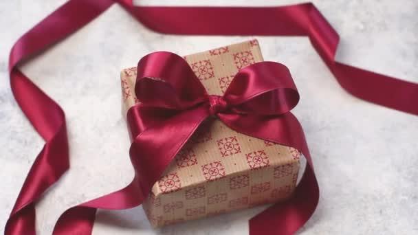 Ajándék doboz sötét piros szatén szalaggal egy fa asztalon