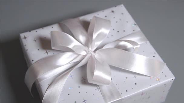Zabalené šedé dárkové krabice s bílou stuhou na šedé