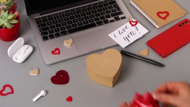 Mladý muž dal luk na Valentýna dárkové krabici poblíž karty, kterou jsem tě miloval