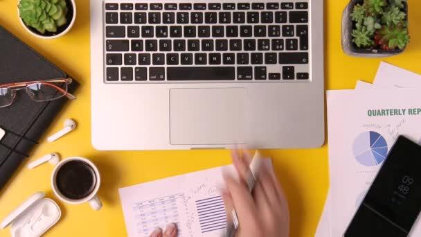 Modern iroda sárga íróasztal és üzletasszony kezét írásban jelentés és gépelés laptop tetejére nézet