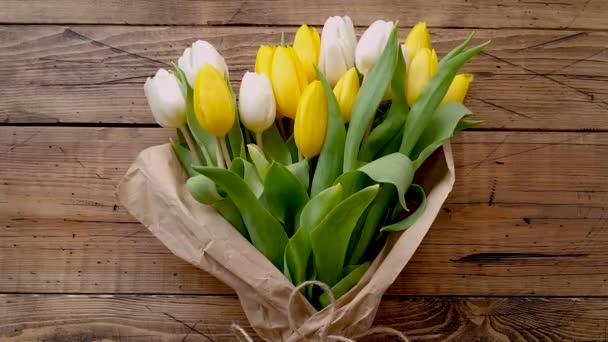 Yellow and white tulips bouquet on a wooden table top view