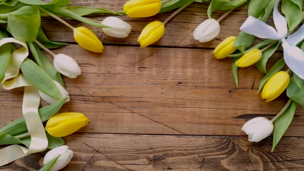 Put a card HAPPY MOTHERS DAY on a wooden table between tulips top view
