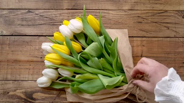 Hands untie a tulips bouquet on a wooden table top view