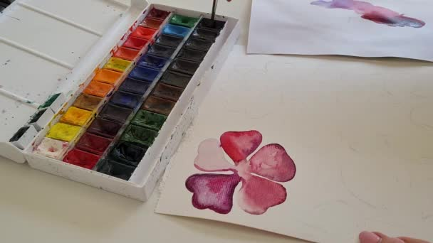 Artists hand paints a purple flower with watercolors close up