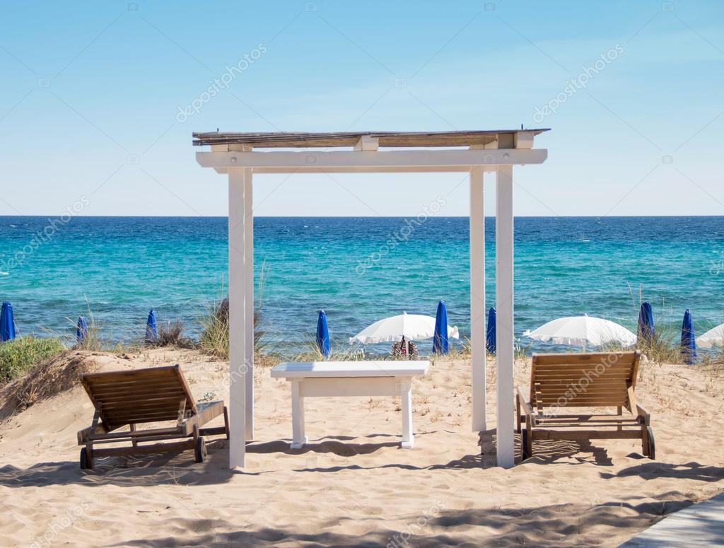 Litorale di mare con gazebo in legno e lettini in spiaggia for Piani per gazebo con camino