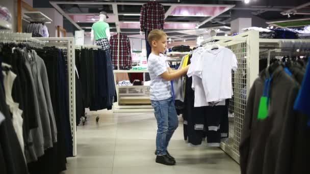 Roztomilý usměvavý chlapec stojí poblíž oblečení a volbou